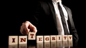 Close up Businessman Arranging Small Wooden Pieces with Integrity Letters on Black Background.