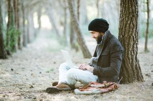 urban man working on laptop while sitting on land in forest
