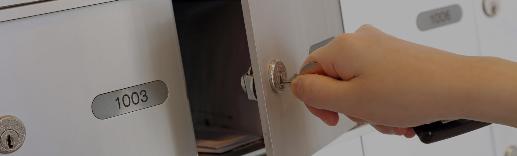 hand opening a mailbox with key